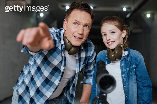 Happy nice man showing something to his daughter