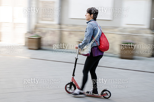 Panning of a woman passing by on a push scooter on street during summer day