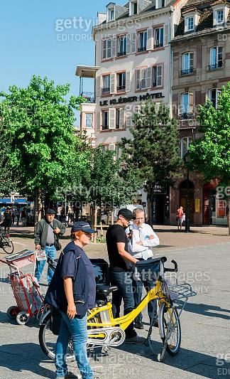 La Poste manger interviewed in city center during exposition of green postal vans