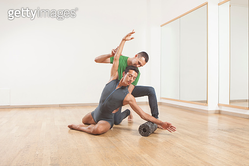 pilates instructor teaching a ballet dancer using foam roller