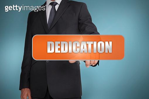 Businessman selecting the word dedication written on orange tag