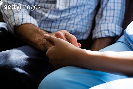 Doctor consoling senior man in retirement home