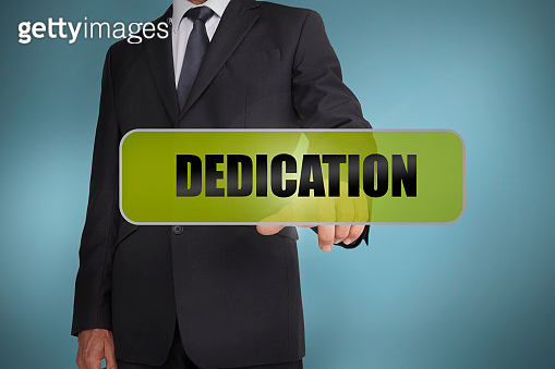 Businessman touching the word dedication written on green tag