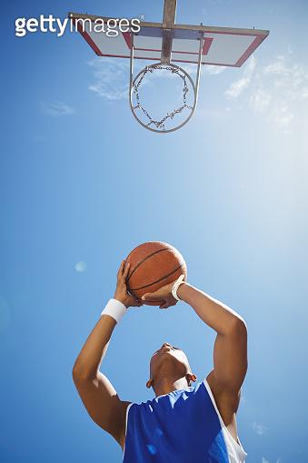 Directly below shot of teenage boy playing basketball