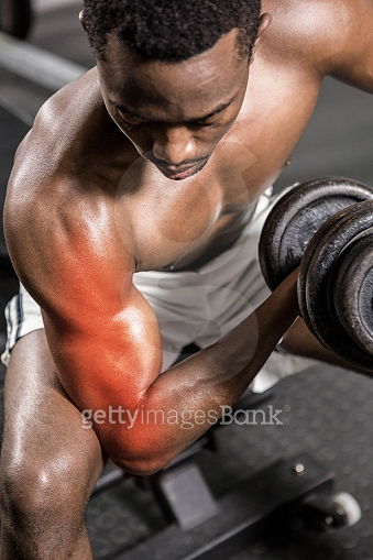 Dedicated shirtless male athlete doing excercise with dumbbells