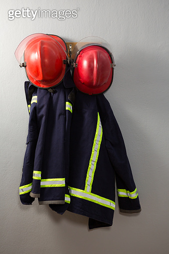 Protective workwear and hard hat hanging on hook