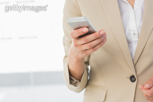 Mid section of a businesswoman text messaging