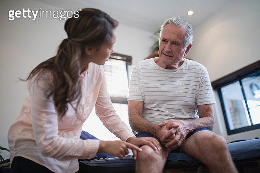 Low angle view of female therapist pointing at knee while male patient sitting on bed