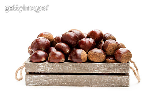 fresh  raw chestnuts in a wooden box isolated on white background