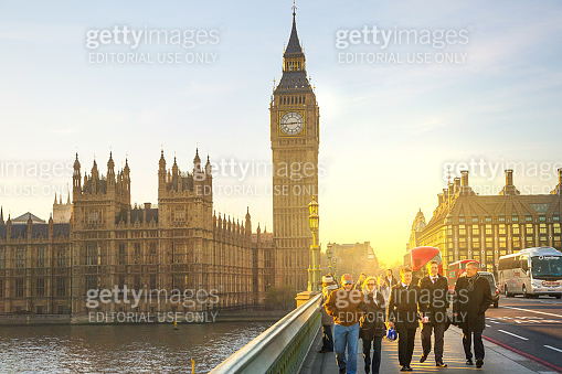 Houses of Parliament and people walking on the River Thames embankment at sunset