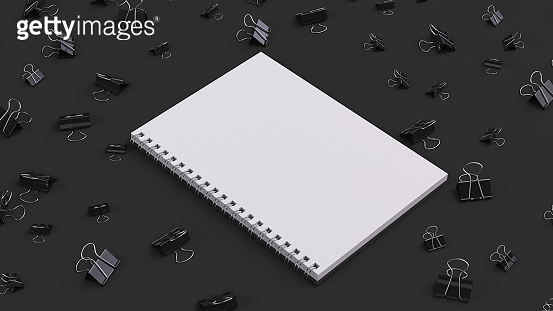 Blank spiral notebook with black binder clips on black table
