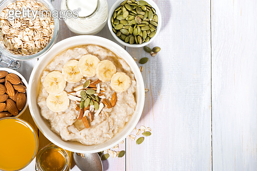 oatmeal with banana, honey and nuts on white background