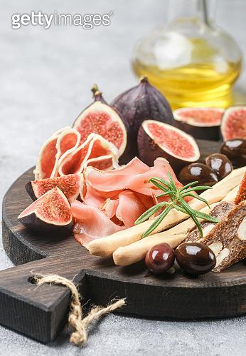 Appetizer of jamon, salami, bread sticks, Kalamata olives and figs on a cutting Board. Italian antipasti. Selective focus
