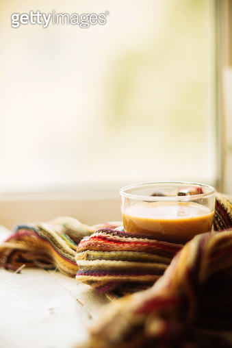 cozy soft gray blanket with a big red cup on the background of a window decorated with frost / warming moments winter holidays