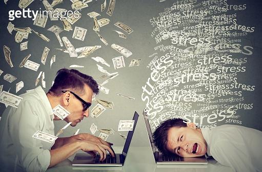 Stressed man working on laptop next to man under money rain.