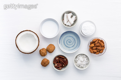Homemade skin care products on white wooden table background. Coconut, oil, walnut, almond, scrub, milk and lotion from top view. Good for space and background.