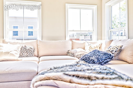 Loft interior space of modern apartment, house or home with staging of large beige, neutral white couches and throw rugs with pillows