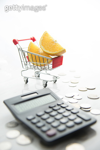 Sliced Orange in the shopping cart with coins.