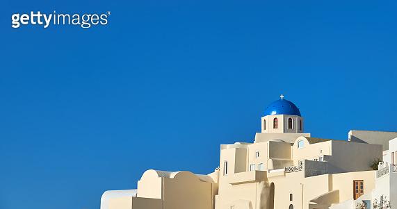 Local church with blue cupola in Oia, Santorini, Greece, panorama