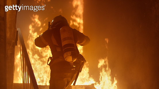 Brave Firefighter With Oxygen Cylinder Runs Up The Stairs. Raging Fire is Seen Everywhere.