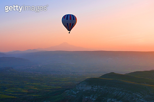 Hot air balloon flying over amazing landscape at sunrise, Cappadocia, Turkey