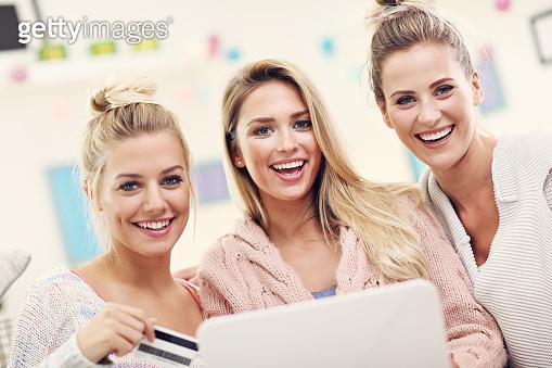 Three beautiful young women shopping online