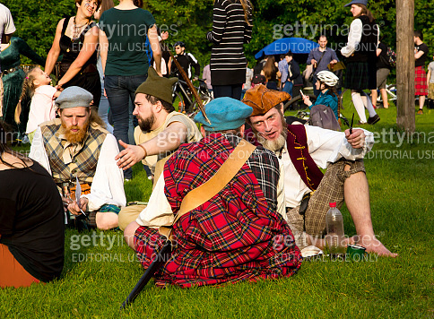 Young people in costumes of Scotland communicate outdoors