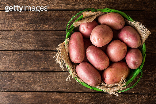 Raw potatoes in basket on wooden background