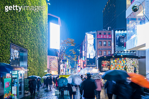 People walking with umbrellas on a rainy day at  Myeong-dong shopping street at night, Seoul, South Korea