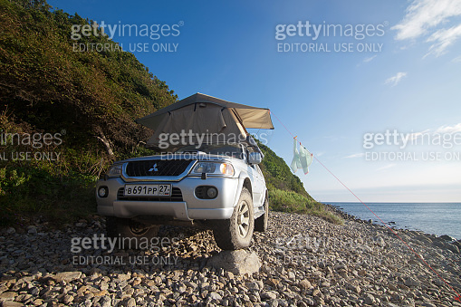 PREOBRAZHENIE, RUSSIA - AUGUST 25, 2014: Mitsubishi Pajero Sport with rooftop tent on a beach