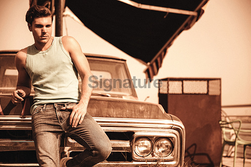 Masculine man standing in front of abandon vehicle
