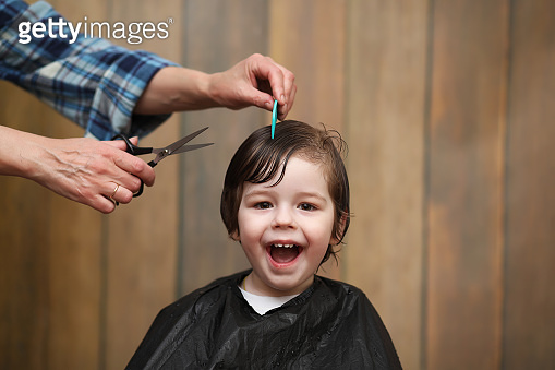 A little boy is trimmed in the hairdresser's bright emotions on