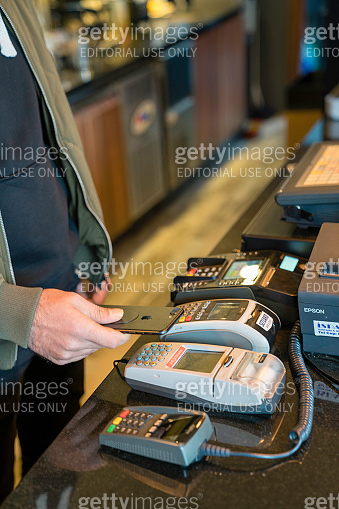 Man using NFC technology on smart phone to pay