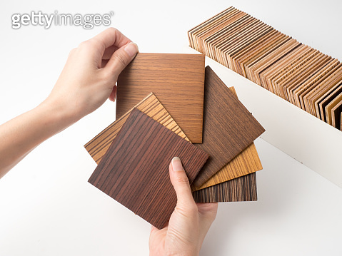 Samples of veneer wood on white background. interior design select material for idea.Hand holding veneer wood.