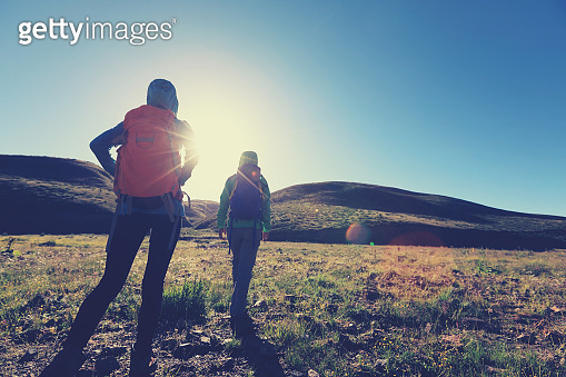 two backpacking women hiking in sunrise mountains