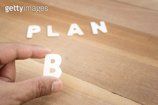 Plan b word with male hand on wood table.Business concepts