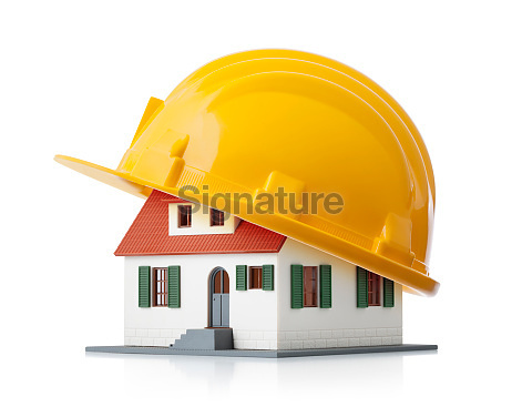 Miniature model house with yellow hardhat