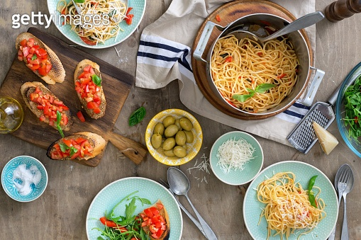 Italian pasta, snacks and salad on a light wooden table, top view