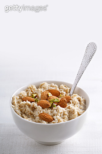 Oatmeal with nuts. Oat porridge in a bowl with spoon and almonds and pistachios.