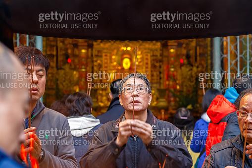 A man praying with burning incense