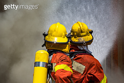 two firefighters fire fighting surround with dark smoke