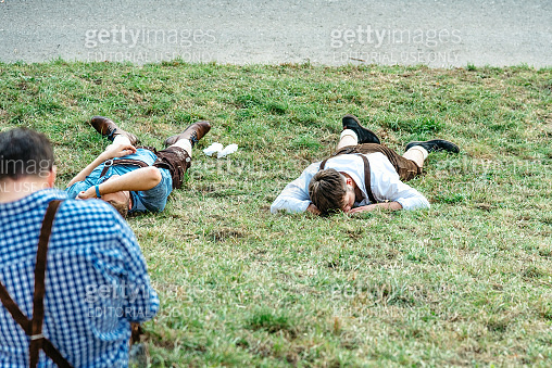 young man resting on meadow at oktoberfest in munich