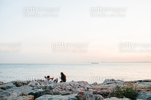 Istanbul, June 14, 2017: Two friends sit on the coast near the sea, communicate and enjoy the view of the Bosphorus and Istanbul. Rest, friendship, holiday.