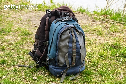 Two touristic backpacks on the riverbank. Hike concept