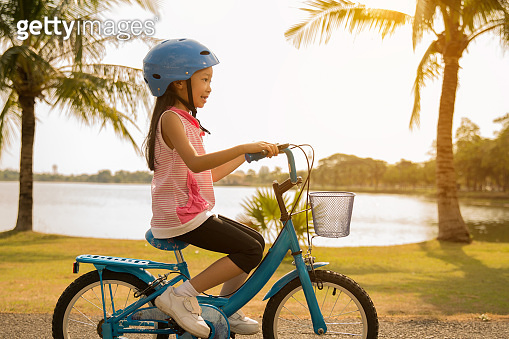 Asian girls cycling at the park in the morning.