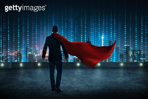 Businessman in a suit and cape hero standing on rooftop with virtual modern city skyline .