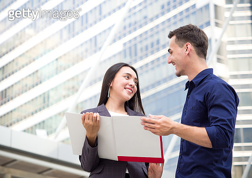 Businesswoman selling insurance to a businessman in city outdoor, showing a contract with happy and smile