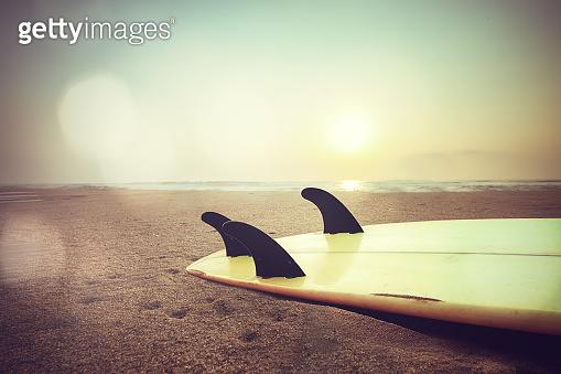 surfboard on beach at sunset