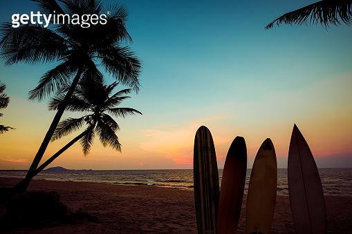 surfboard on tropical beach at sunse