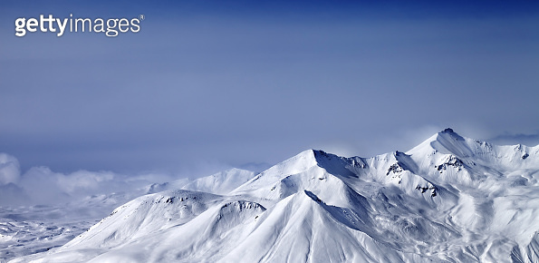 Panoramic view on snowy mountains in mist at winter evening